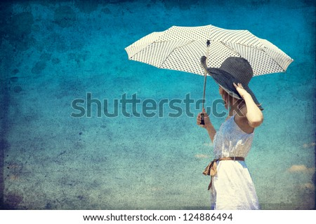 Redhead girl with umbrella at outdoor. - stock photo