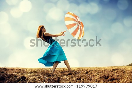 Redhead girl with umbrella at windy field.