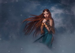 redhead goddess fantasy woman walks in the clouds. Fashion model posing in studio background dramatic winter sky with smoke. Elf princess girl. Long red hair flying in wind snow is falling. Blue dress