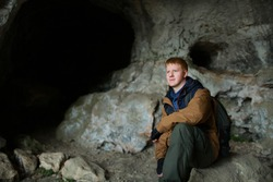 Redhead man in a brown-and-blue windbreaker sits in a cave in the cave city of Mangup-Kale in the Crimea near the city of Bakhchisaray. Travel, adventure, hiking, motivation and speleology concept.