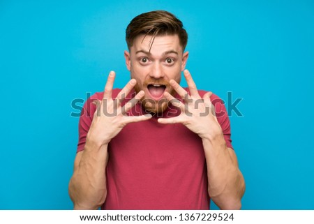 Redhead man on isolated blue wall with surprise facial expression #1367229524