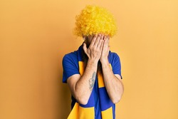 Redhead man with long beard football hooligan cheering game wearing funny wig with sad expression covering face with hands while crying. depression concept.