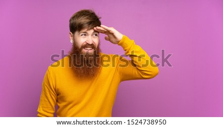 Redhead man with long beard over isolated purple background looking far away with hand to look something