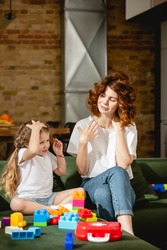 redhead mother looking at adorable daughter near building blocks