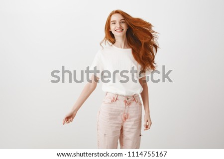 Redhead rule world. Portrait of carefree happy and charming female with ginger hair, jumping joyfully over gray background, smiling at camera, having fun and being amused, expressing joy and happiness