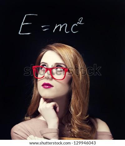 Redhead student near blackboard. - stock photo