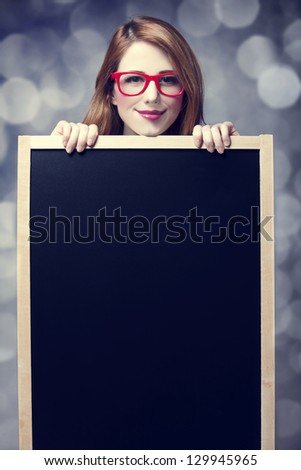 Redhead student with blackboard. - stock photo
