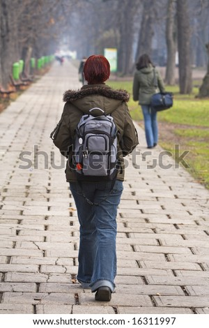 Redhead teen with backpack walking in an autumn park. - stock photo