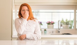 Redhead woman at kitchen smelling something stinky and disgusting, intolerable smell, holding breath with fingers on nose. Bad smells concept.