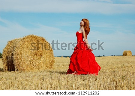 redhead woman in a red dress at village outdoor.