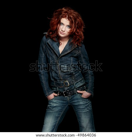 Redhead woman in jeans close up portrait, over black background