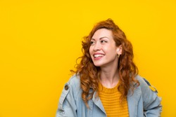 Redhead woman over isolated yellow background laughing and looking up