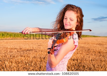 Redhead woman playing violin outdoors on the field in summer evening