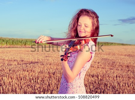 Redhead woman playing violin outdoors on the field in summer evening. Split toning.