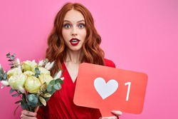 redhead woman posing isolated over pink wall background holding like symbol sign and bouquet of flowers, she is in shock, stand with wide opened mouth