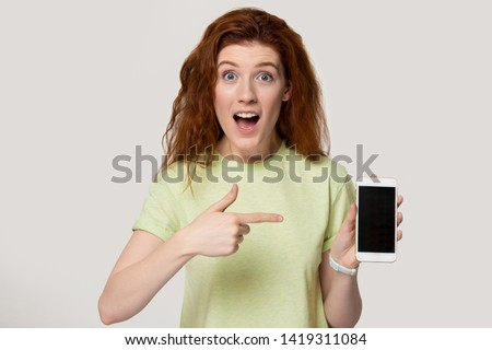 Redhead woman show phone white blank mock up ad screen look at camera feels amazed stunned, shopper girl surprised by new free app, big discounts, cheap flights traveling ticket, better offers concept