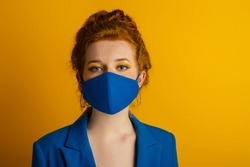 Redhead woman wearing trendy fashion blue monochrome outfit with  protective face mask. Model has matching bold eyes makeup. Style during quarantine of coronavirus outbreak. Copy, empty space for text