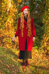 Redhead woman with long hair in red coat on autumn background. Girl with red hair on background of forest with orange autumn leaves. Red turban and fashion autumn coat. Redhead fashion model