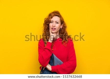 Redhead woman with overalls over isolated yellow wall thinking an idea