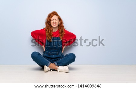 Redhead woman with overalls sitting on the floor suffering from backache for having made an effort