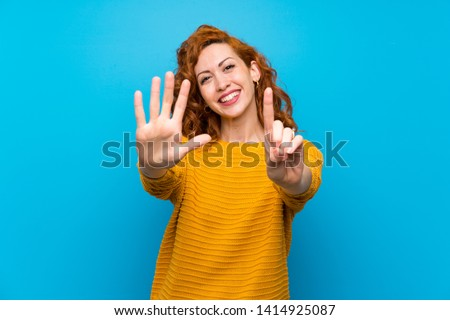 Redhead woman with yellow sweater counting six with fingers Foto stock ©