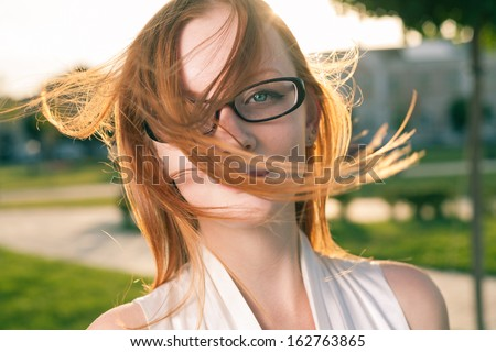 redhead women weared glasses  with hair fly by the wind, outdoors