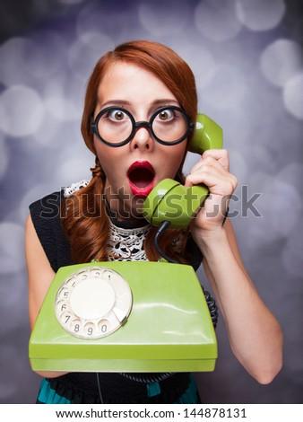 Redhead women with green telephone. - stock photo