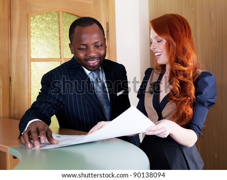 Redhead young business woman and black american business man smiling