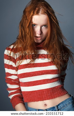 redhead young sweet girl in the studio wearing a sweater, tenderness, femininity, sexy
