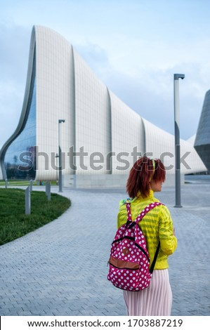 redhead young woman in a yellow jacket with a backpack against the background of the unusual architecture of the city of Baku