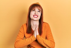 Redhead young woman wearing casual orange sweater begging and praying with hands together with hope expression on face very emotional and worried. begging.