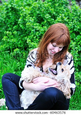 redheaded pretty girl playing with her dog on the meadow