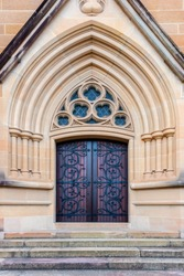 Redish brown church entrance door with ornate wrought iron recessed into an ornate  textured sandstone pointed archway.
