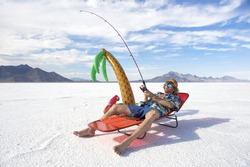 Redneck American fisherman wearing Hawaiian shirt goes on cheap ice fishing vacation holiday with inflatable palm tree in white desert
