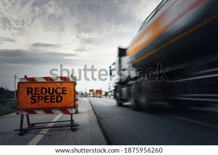 Reduce speed road sign on a countryside road with blurry speed truck,dark and dramatic scene with low-speed shutter. Photo stock ©