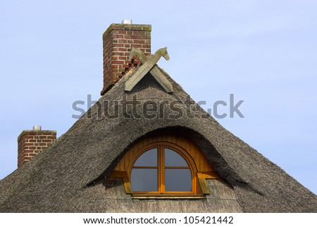 Reed-covered roof - Reed-covered roof of a typical Northern German residential house, with single window and gable decoration. - stock photo