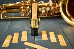 Reed mounted on saxophone mouthpiece, set of replacement reeds and the instrument at the bottom