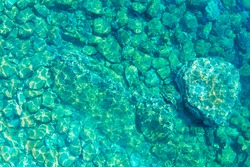 Reef and rocks on sea floor are visible through clear turquoise water, glare of the sun is reflected from surface of water, top view from height, drone shooting.
