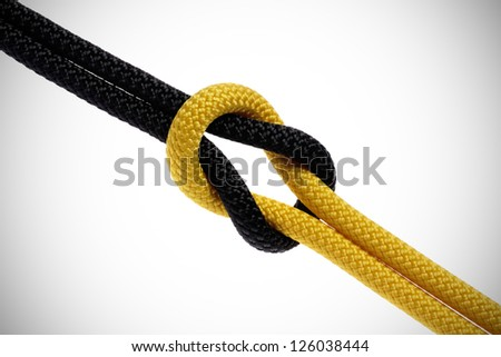 Reef-knot of black and yellow rope. isolated on white background