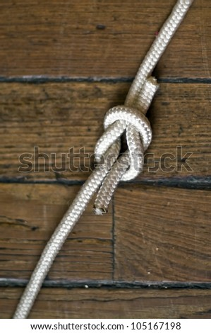 Reef knot over the wooden background