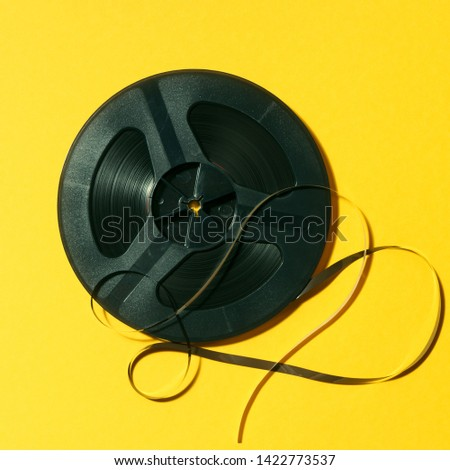 reel-to-reel tape in spool on a yellow background #1422773537