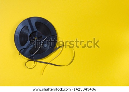 reel-to-reel tape in spool on a yellow background #1423343486