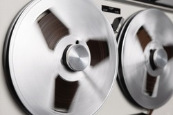 Reel to reel tape recorder playing. Rotating retro tape. Vintage music player close up. Spinning reels metallic color. Party. Loop. Macro. Side view. Popular Disco Trends 60s, 70s, 80s, 90s