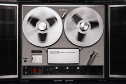 Reel to reel tape recorder playing. Rotating vintage music player close up. Retro tape. Spinning reels metallic color. View from above. Popular Disco Trends 60s, 70s, 80s, 90s.