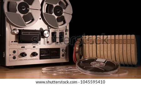 Reel to Reel taperecorder playing music isolated on black background and space for copy #1045595410