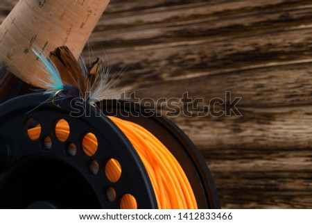 reel with orange fishing line and feather bait lie on a wooden background #1412833466