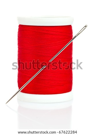 Reel with red thread and needle on a white background with reflections