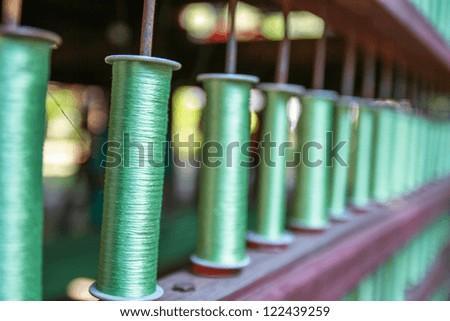 Reels of green silk threads pattern - stock photo