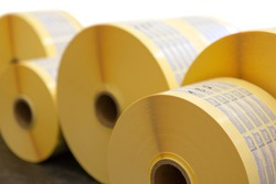 Reels of printed adhesive labels before slitting or cutting isolated on white background. Bunch of printed rolls.