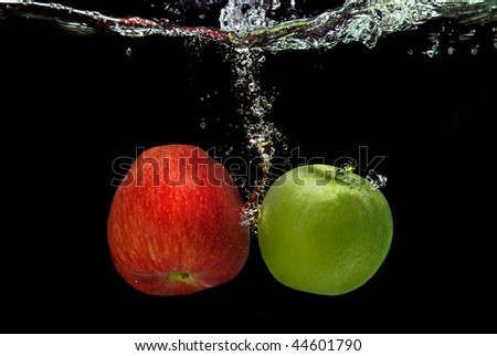 ref and green apple dropped into water with splash isolated on black
